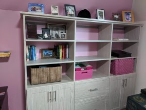 Shelving unit built by Closets, etc. for an Angie's List customer with a wood-look finish for 9 shelves above cabinets and drawers.
