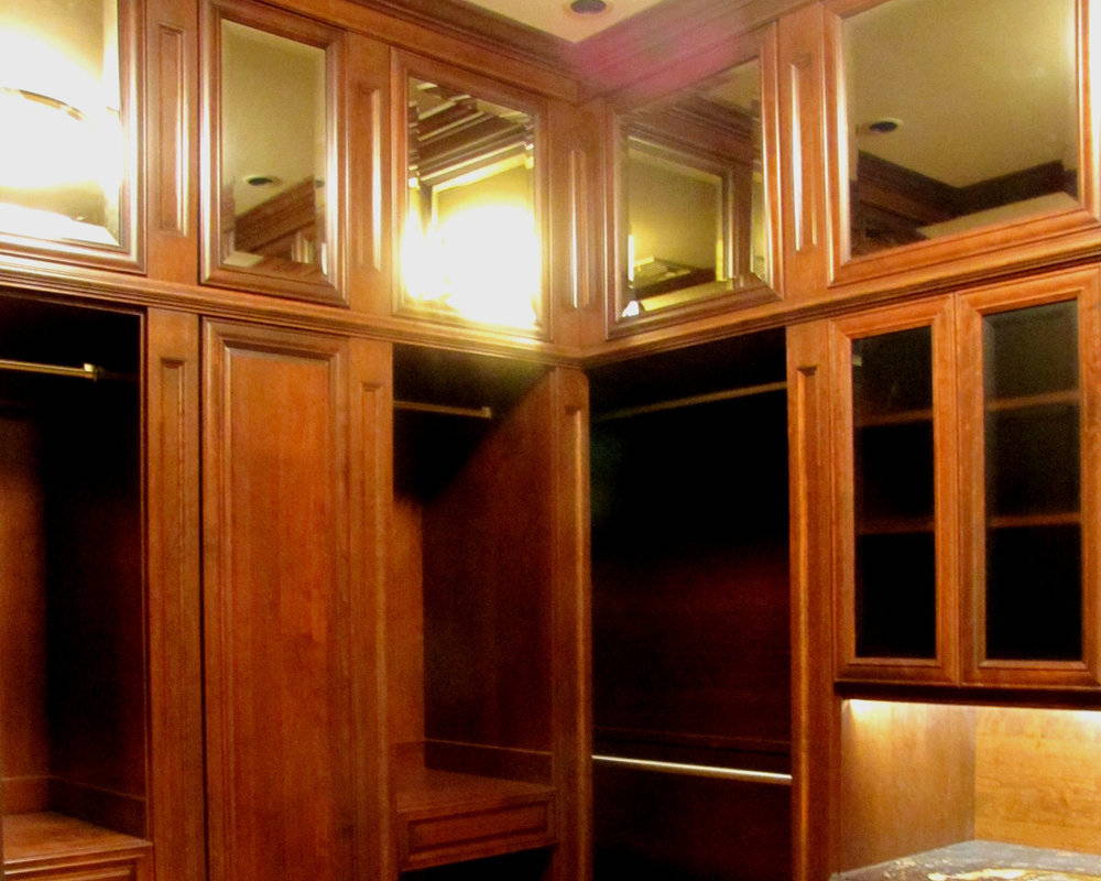 Large walk-in closet fabricated in solid wood, with floor-to-ceiling storage options and mirrored upper cabinets.